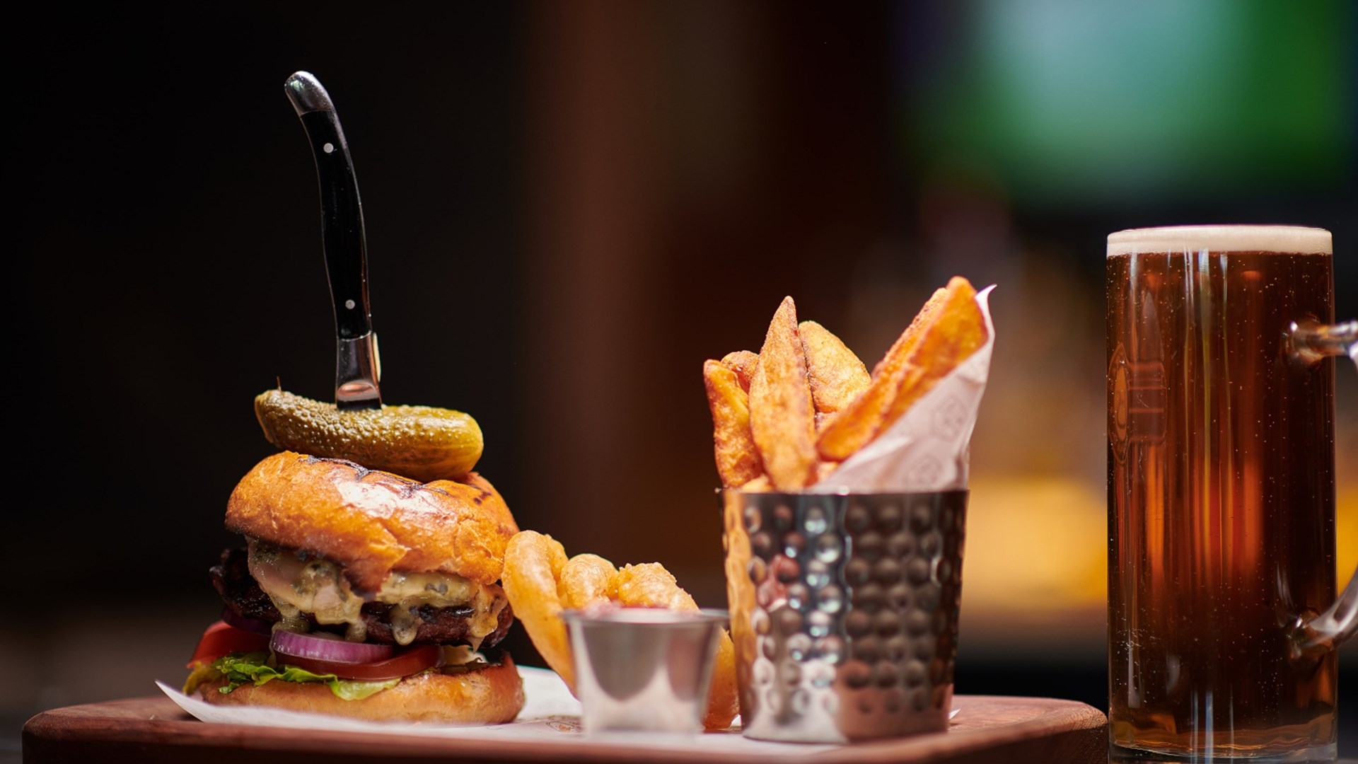 Close up of burger, chips and onion rings laid on a platter, alongside a pint of beer.