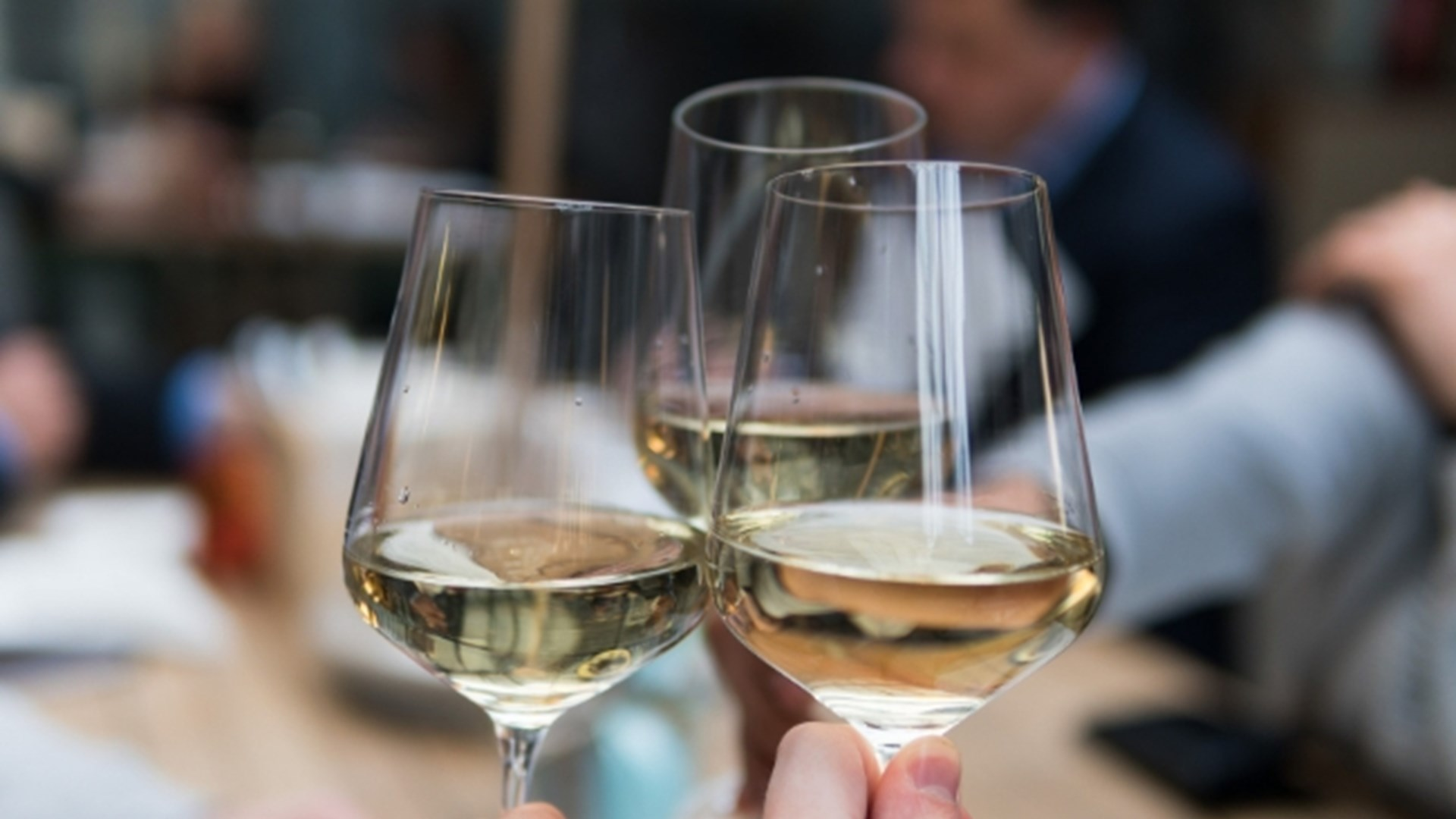 Close up of three white wine glasses clinking together