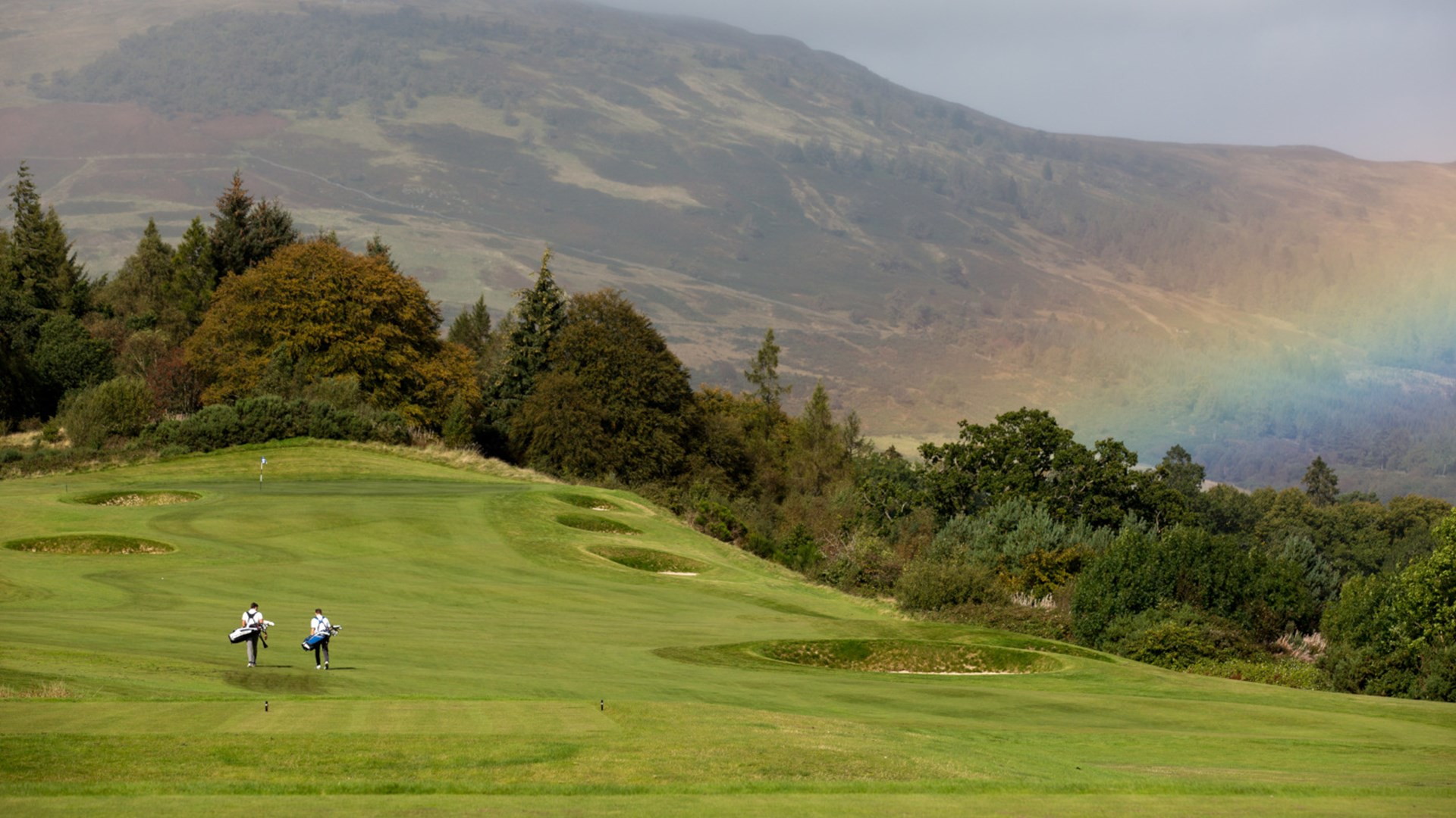Wide view of gold course as two golfers walk across with mountains and the Trossachs forest in the distance.
