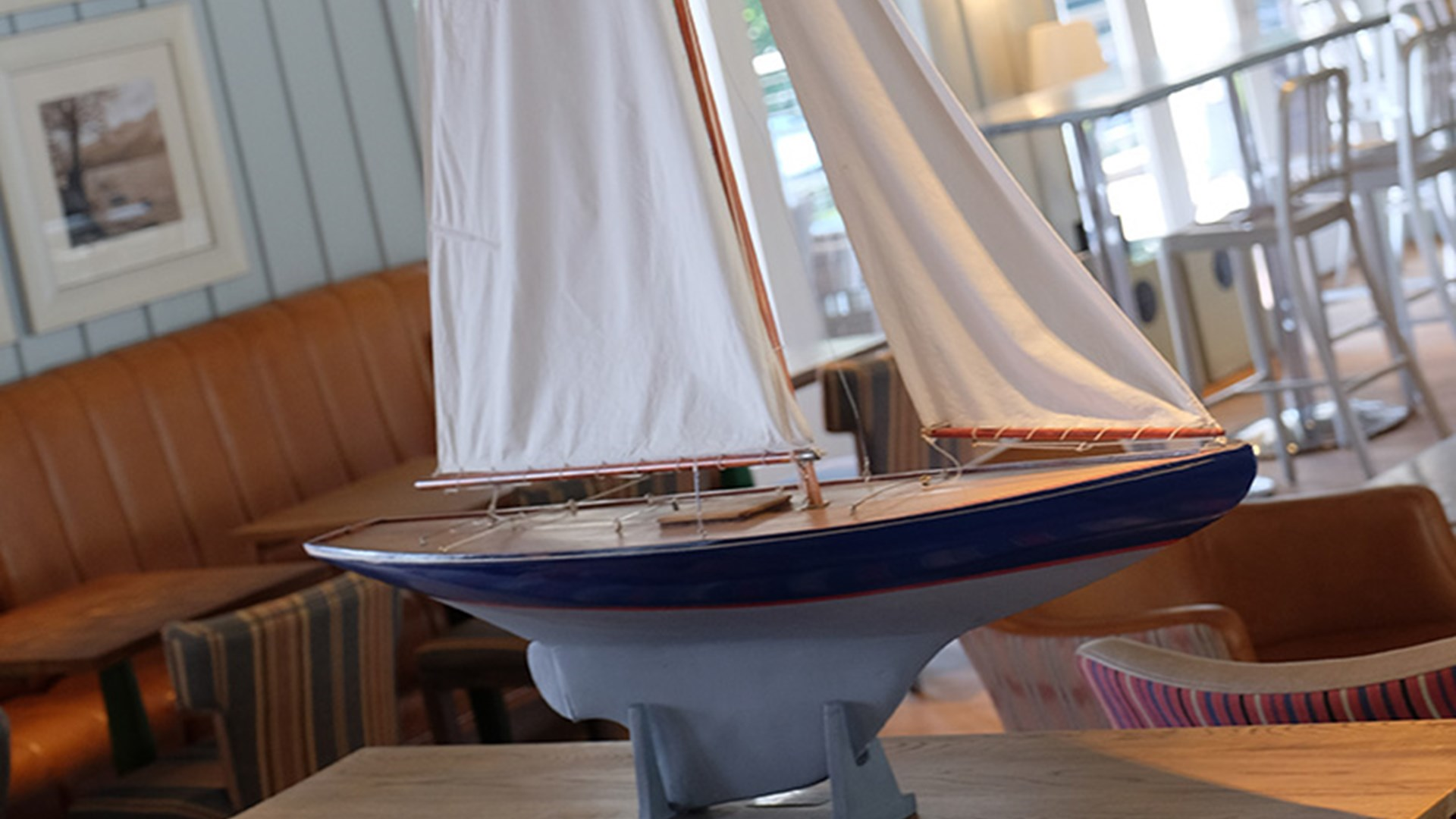 Large model sailboat used as decoration atop a table in the boat house bar