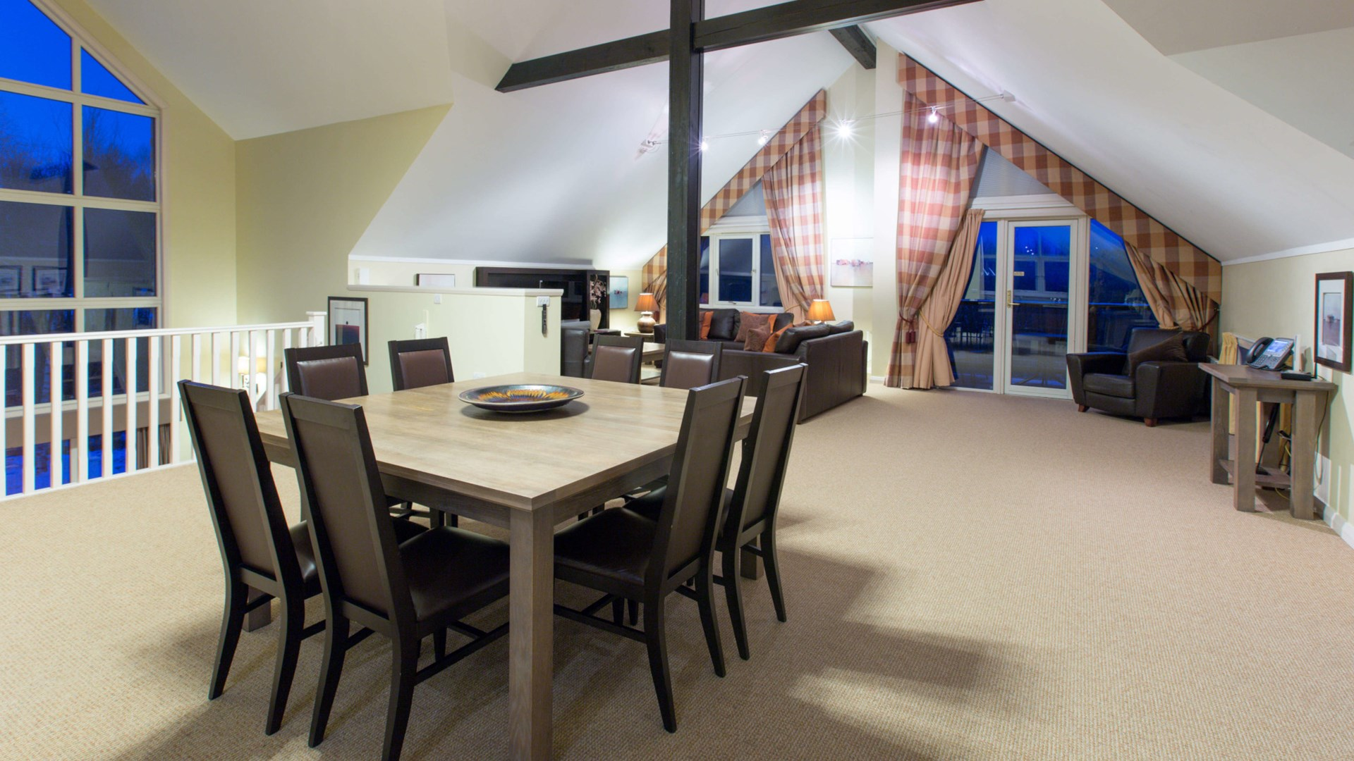 Spacious living and dining areas with exposed wood beams and floor length windows, within four bedroom detached lodge.