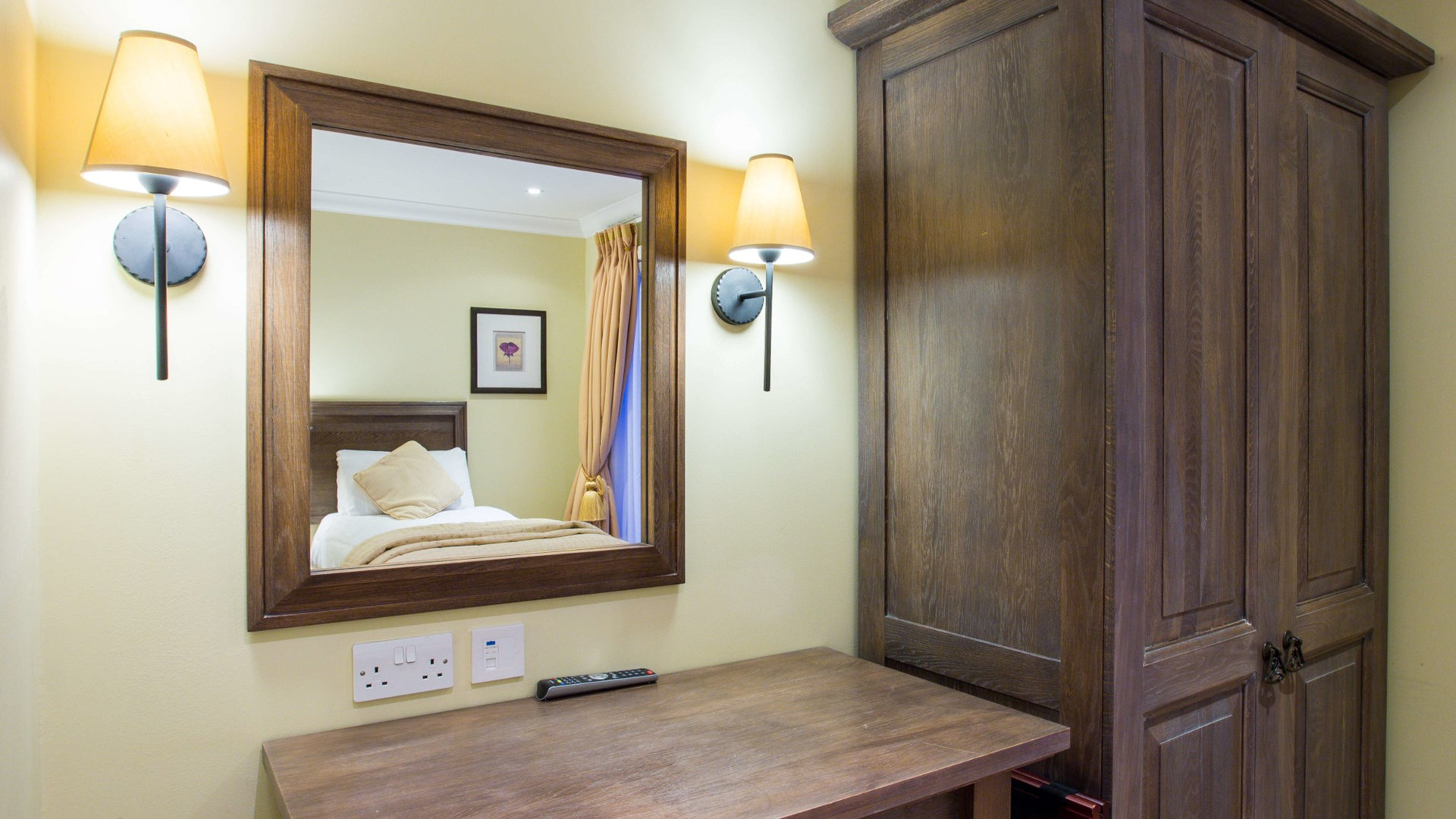 View of bed reflected in the mirror, within a four bedroom detached lodges at Cameron Club