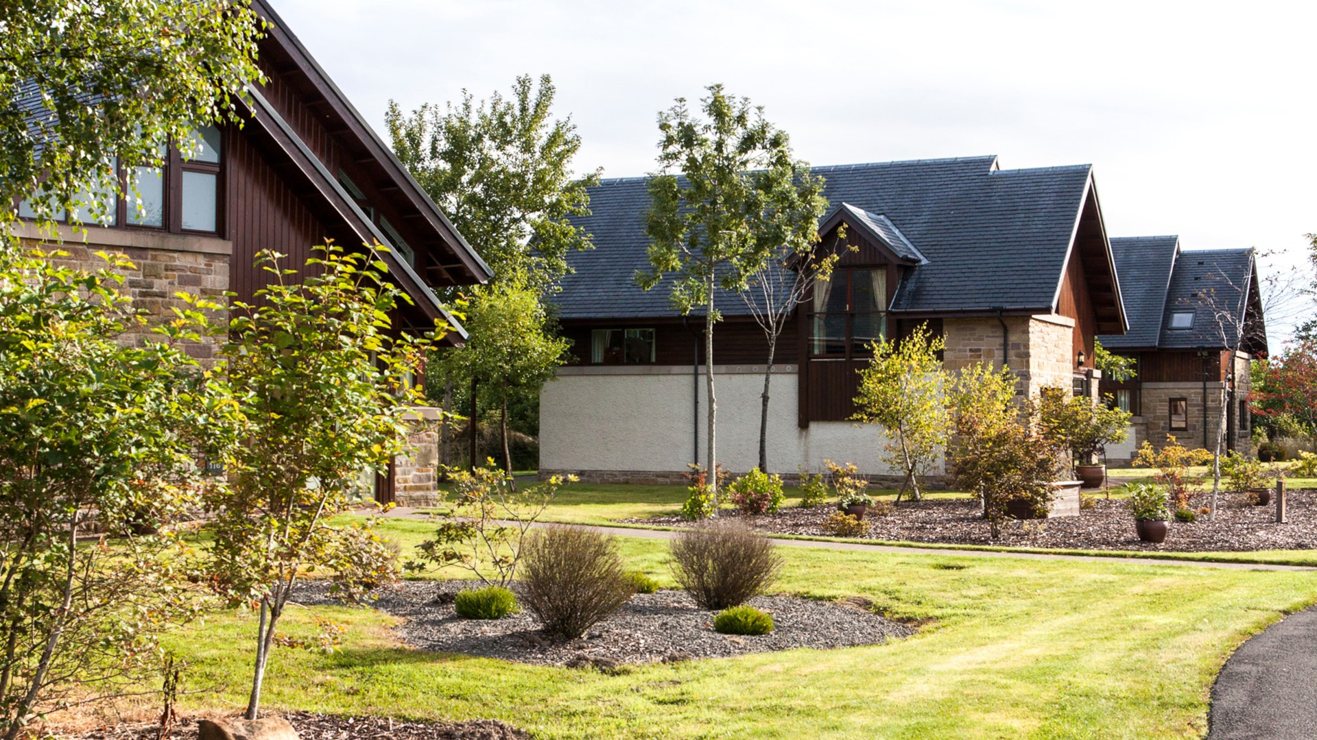Exterior of four-bedroom detached lodges and the surrounding gardens at Cameron Club on a sunny day.