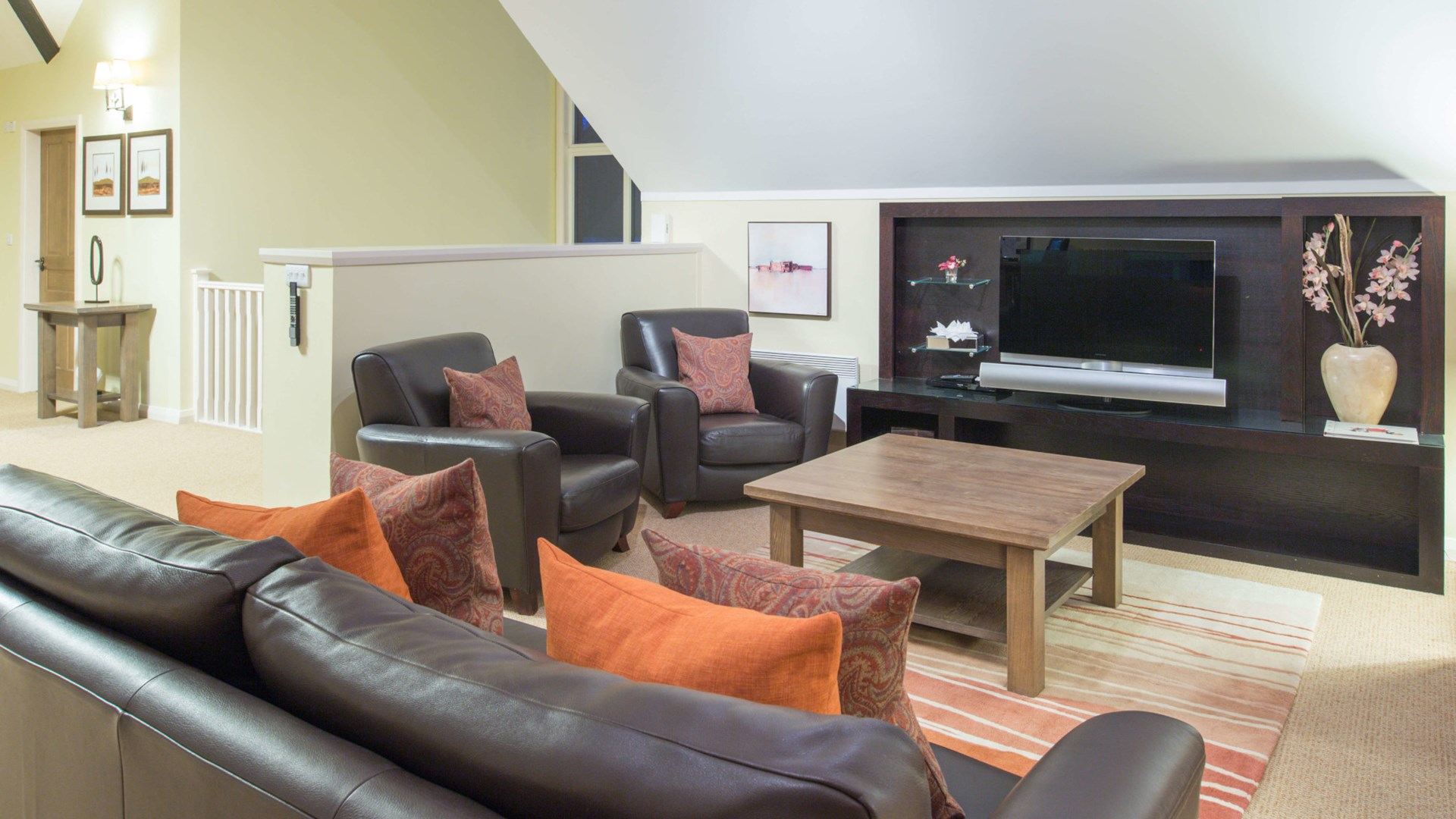 Lounge area with couches wooden table and TV within four bedroom detached lodge at Cameron Club.